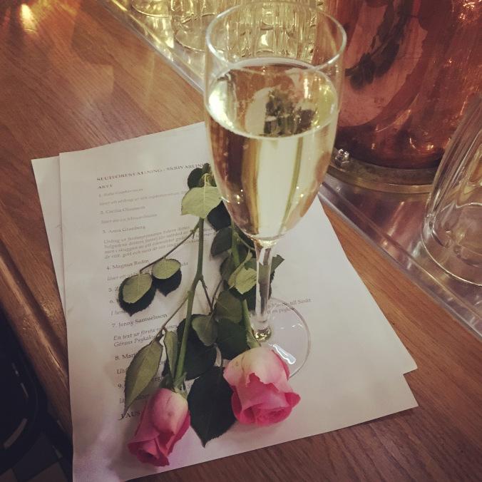 Ett glas prosecco och två rosa rosor på ett programblad.